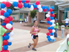 Excited Woman Running Through Balloon Archway