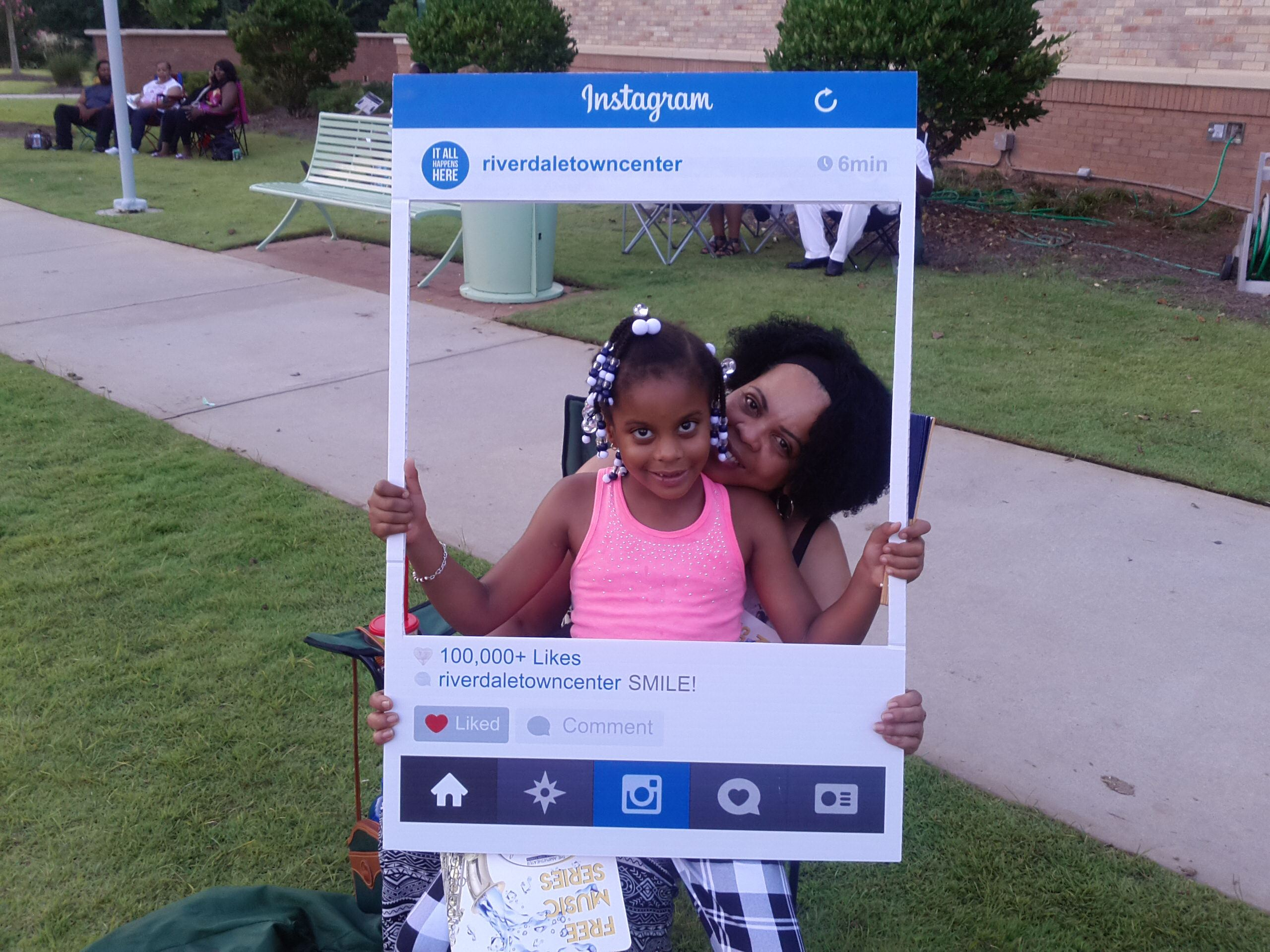 Woman and Little Girl Posing with Instagram Cut Out