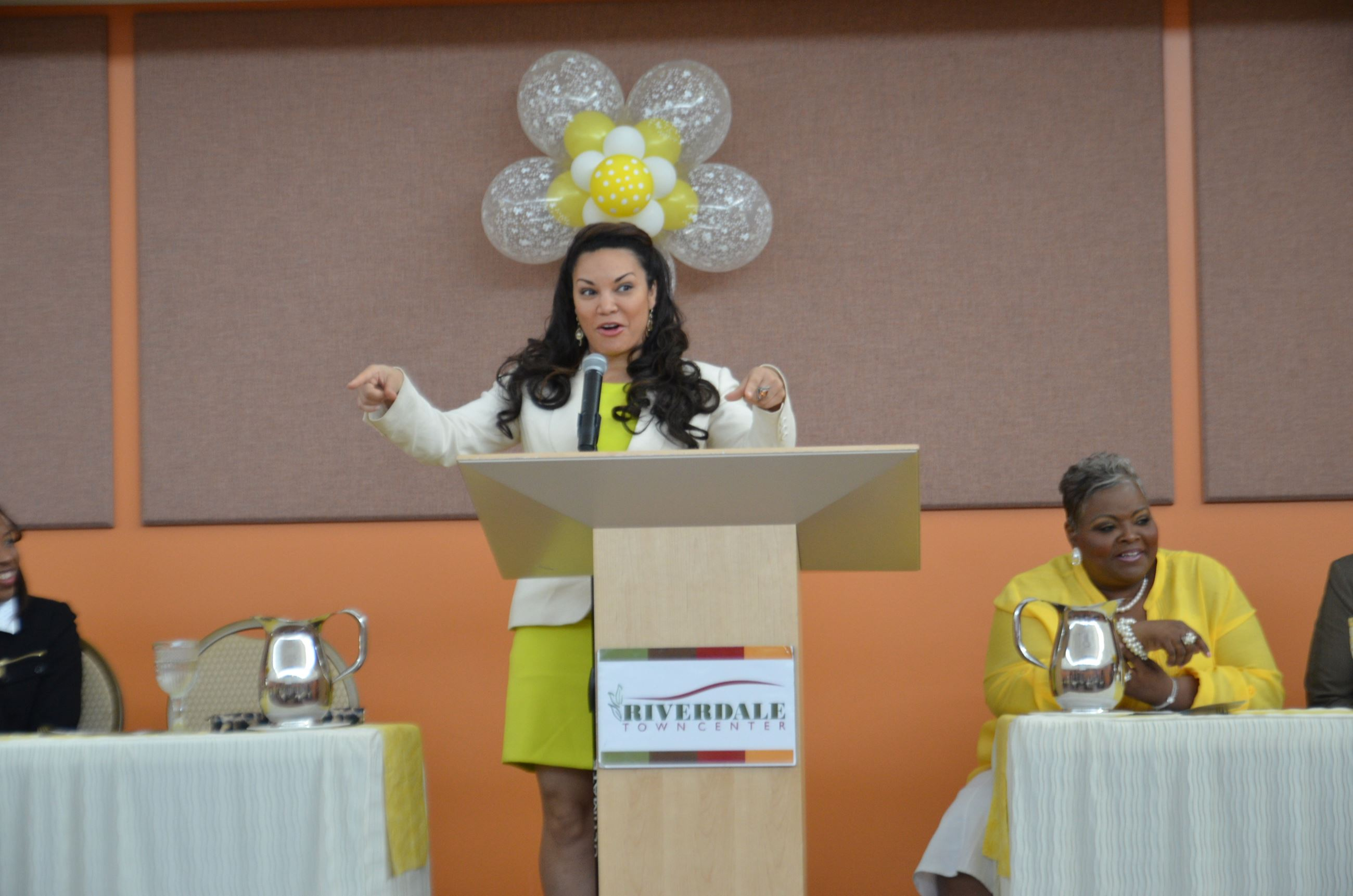 Woman Pointing While Speaking at Podium
